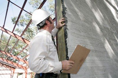 877088-a-building-inspector-checking-over-incomplete-stucco-work-on-new-construction-focus-on-stucco-work